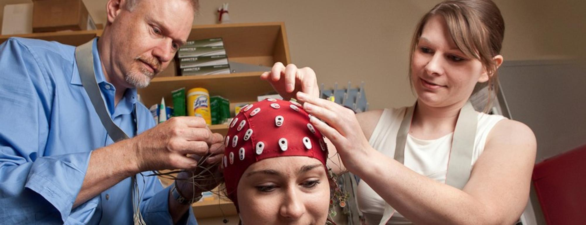 professor and researcher applying EEG leads to a research participant