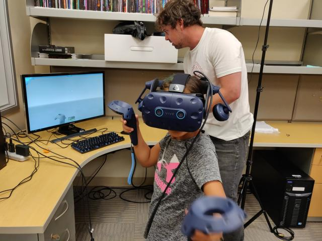 researcher with a child who is using virtual reality gear