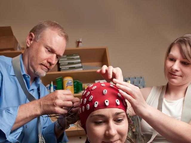 researchers placing a cap with leads on a participant's scalp